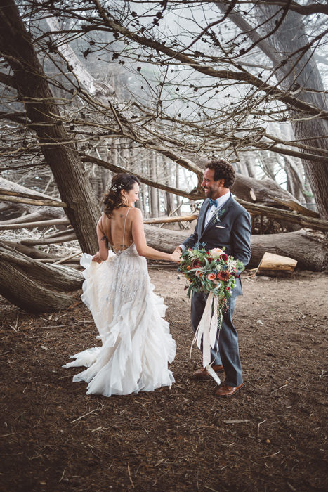 A couple on their wedding day in Big Sur, California. Groom holding brides bouquet of protea, david austin roses, flowy ribbons